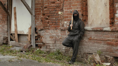 Hooligan in black mask and hood with baseball bat leaning back on brick wall Live Action