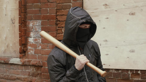 Street bandit in black mask and hood holds baseball bat in criminal district Live Action