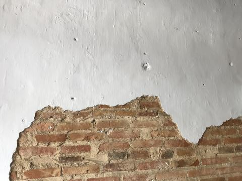 white wall with cracked space which shows red brown bricks inside Photo