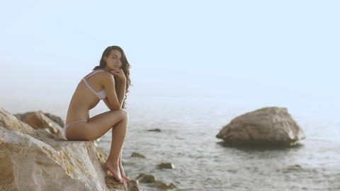 Portrait of beautiful young woman on wild rocky beach Stock Video Footage