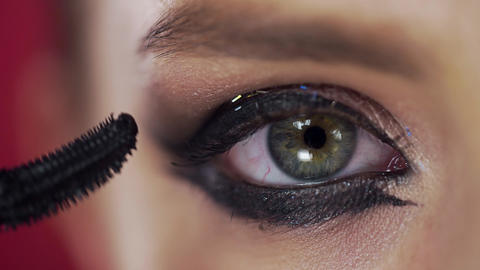 Close up of the eye lashes makeup, woman with evening makeup paints lashes, eye Footage