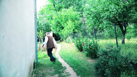 Old man quickly walking by the house GIF