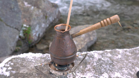On a portable gas burner, there is a kettle for brewing coffee. Picnic near the Footage