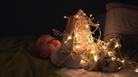 Happy baby boy play with tangled LED garland shining in different modes Footage