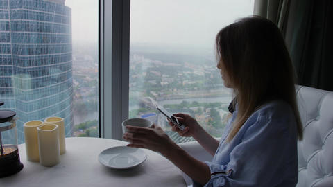 Young woman in casual wear with cellphone drinks coffee. Rainy cityscape in Footage