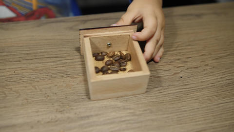 Baby sets small wooden box with beans in manual coffee grinder. Close up of Footage