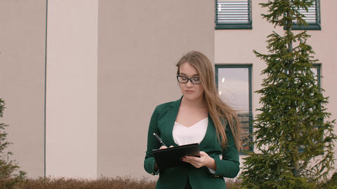 Business woman in glasses and business suit writes... Stock Video Footage