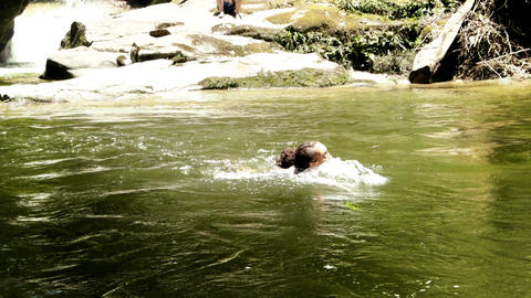 Young woman swimming in river by mountain Live Action