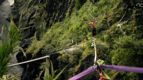 Extremal male balancing on slackline or tightrope high above the ground with Live Action