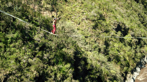 athletic walking on slackline or tightrope over green forest Live Action