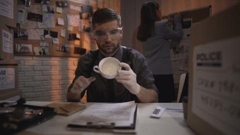 Research specialist taking fingerprints from white coffee cup on the table Live Action