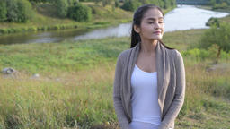 Young happy Asian woman thinking against relaxing view of nature Footage