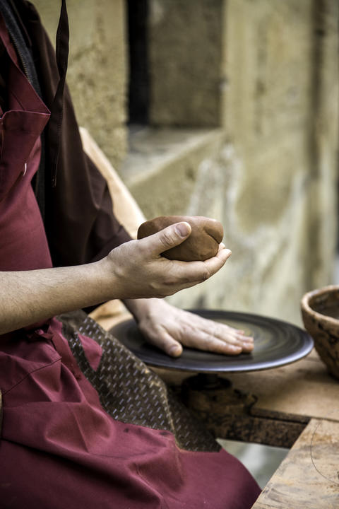 Hands of man working and shaping clay, potter in pottery フォト