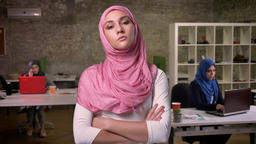 Calm arab girl in pink hijab is standing with her pink hijab in the brick office Footage