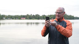 Happy Senior Man Using Phone By The Lake Footage