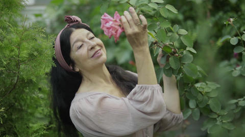 Mature woman smelling a rose in the garden Live Action