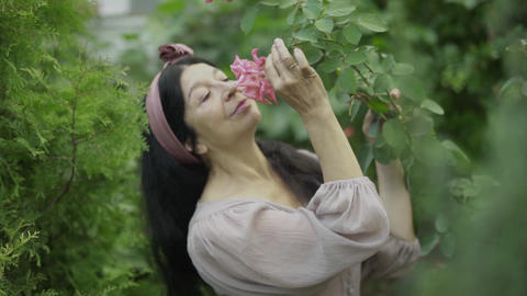 Mature woman smelling a rose in the garden, Live Action