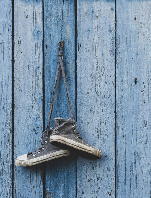 very old textile sneakers hanging on a nail Photo