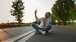Young woman taking selfie on road. Lovely young lady smiling and posing for Live Action