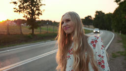 Young woman hitchhiking on countryside road Footage