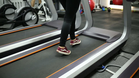 Girl runs on the treadmill in the gym Live Action