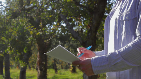 One unrecognizable farmer sign papers in the apple orchard Footage