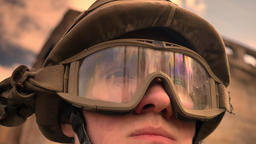 Close-up face of caucasian soldier in helmet with sky and sunshine reflection on Footage