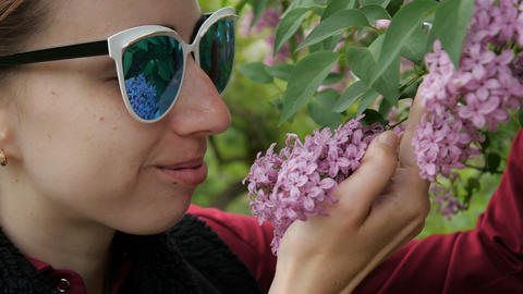 A girl in white sunglasses smells a lilac GIF