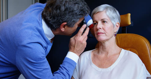 Optometrist examining patient eyes with ophthalmoscope 4k Live Action
