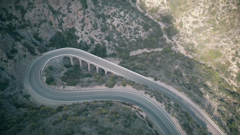 Aerial view of sharp hairpin turn in mountains Live Action