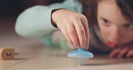 Close up shot of a girl spinning a Hanukka dreidel on the floor GIF
