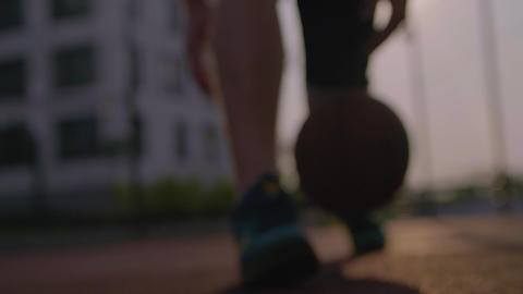 Basketball player dribbles the ball in urban court GIF