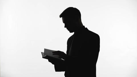 Silhouette of young businessman reading book, planning startup, ideas for future Footage