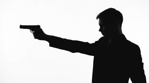 Silhouette of cold-blooded killer pointing handgun, revenge, contract killing Live Action