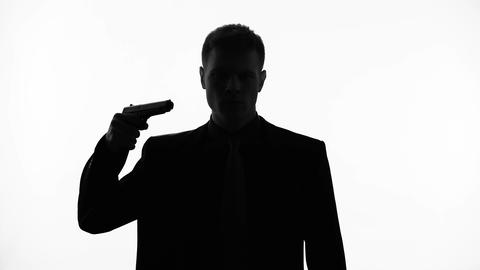 Man silhouette feel uncertain about committing suicide, pointing gun at his head Live Action