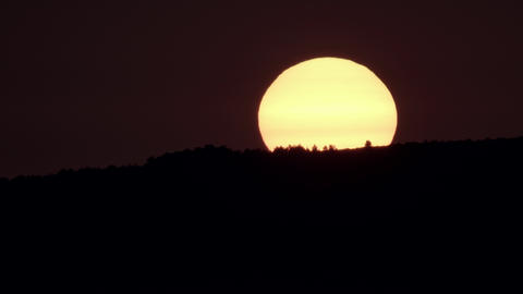 Sunrise behind dark hill and huge orange sun Live Action
