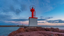 Sunset sky timelapse in marina entrance with lighthouse Footage