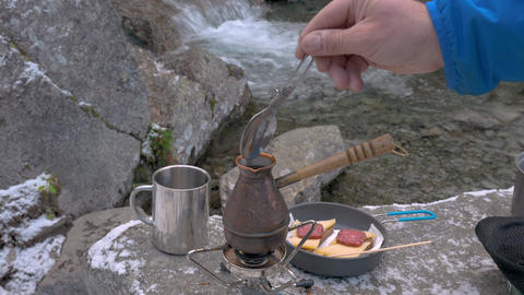 On a portable gas burner there is a kettle. Coffee is thrown into it. Picnic Live Action