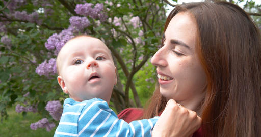 4K - Young mother kisses the baby in the park Footage