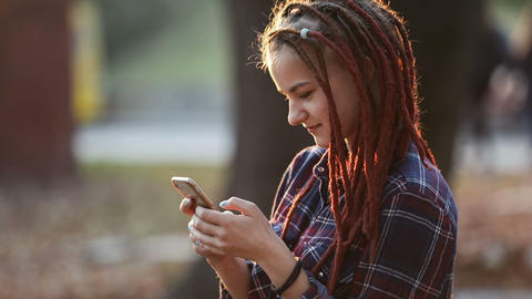 Teenager Uses Phone in Park Live Action