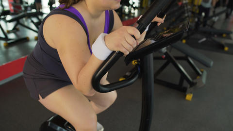 Overweight female suffering from labored breathing sitting on stationary bike Live Action