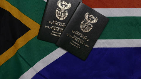 Flatlay Throwing on multiple SA passport on flag Live Action