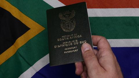 Flatlay Handing over and put down RSA passport on SA flag Live Action