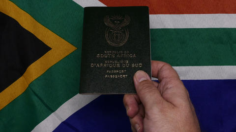 Flatlay Handing over South African passport on SA flag Live Action