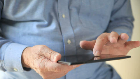 Man with tremor uses tablet Footage