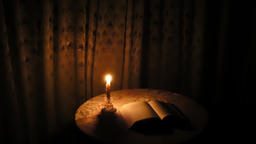 Book on the table with the candle GIF