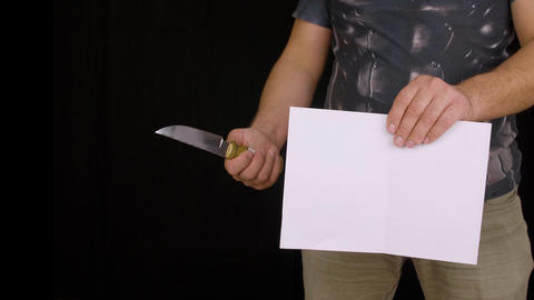 Male hand holding knife and testing sharp blade on paper on black background Live Action