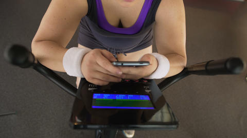 Obese woman scrolling on cellphone while riding exercise bike, fitness app Footage
