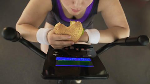 Corpulent female eating fatty burger while riding stationary bike, fast food Footage