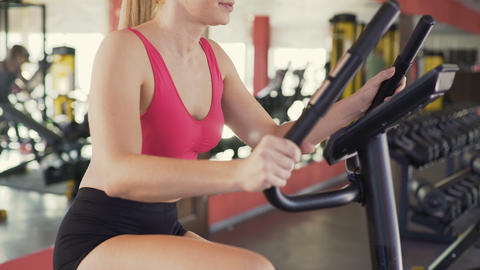 Slim woman riding exercise bike at sports club, healthy lifestyle, sports Live Action